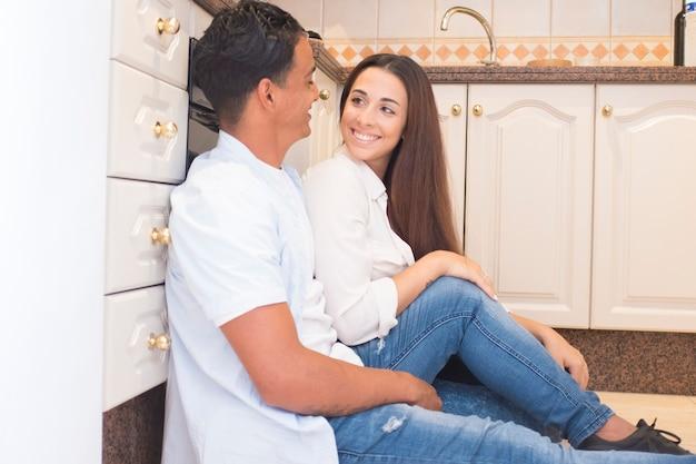Szczęśliwa młoda para cieszy się nowym mieszkaniem w domu razem siedząc na podłodze w kuchni - koncepcja ludzi miłości i życia z wesołym mężczyzną i kobietą, patrząc i uśmiechając się