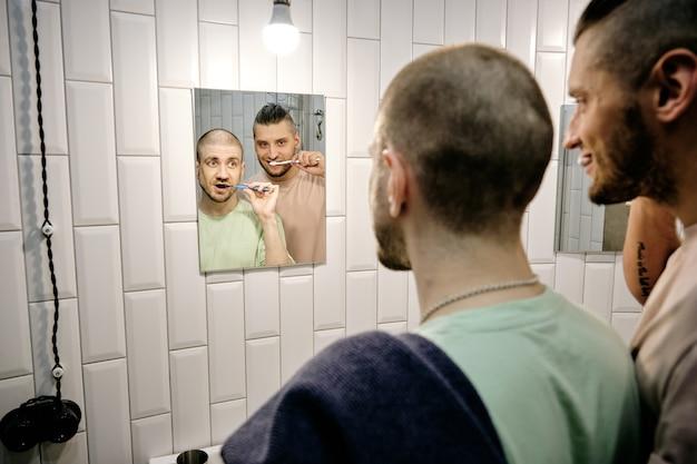 Szczęśliwa młoda para homoseksualna myjąca zęby i patrząca w lustro w łazience