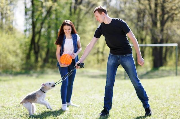 Szczęśliwa młoda para i ich pies w parku