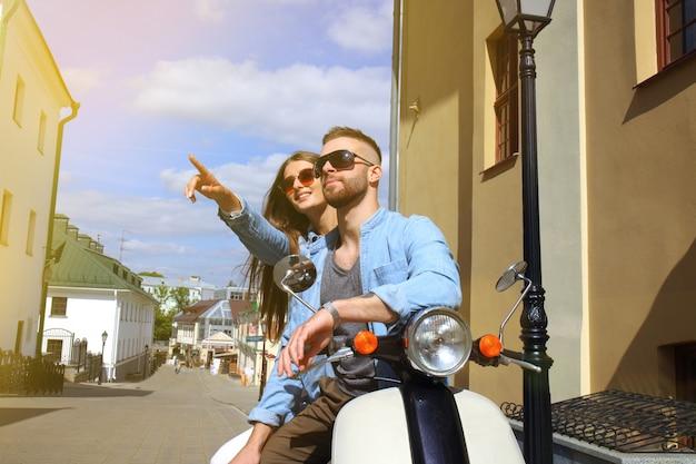 Szczęśliwa młoda para jazda skuterem w mieście. przystojny facet i młoda kobieta podróż. koncepcja przygody i wakacji.