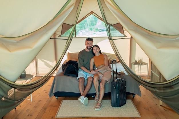 Szczęśliwa młoda para kaukaska relaksuje się na łóżku w domu glampingowym