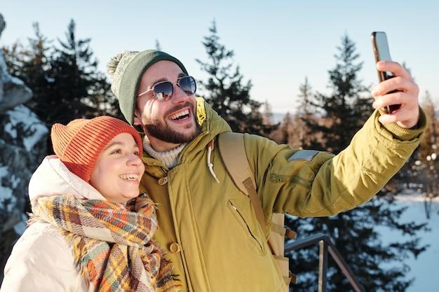 Szczęśliwa młoda para kaukaska robi selfie w lesie