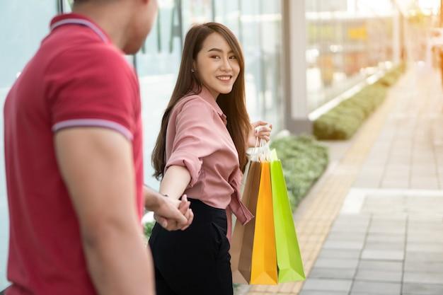 Szczęśliwa młoda para kupujących chodzących na ulicy handlowej w kierunku zakupy w czarny piątek