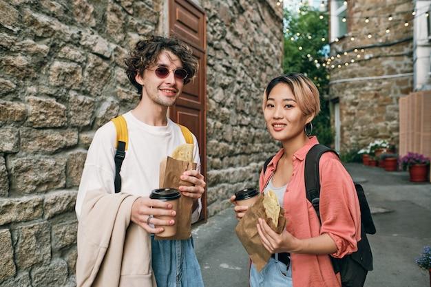 Szczęśliwa młoda para międzykulturowa mająca fastfood z napojami