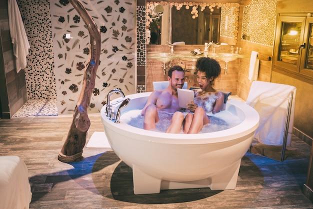 Szczęśliwa młoda para międzyrasowa zrelaksowała się, ciesząc się sobą w jacuzzi, pijąc wino i tabletkę