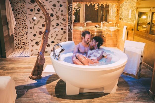Szczęśliwa młoda para międzyrasowa zrelaksowała się, ciesząc się sobą w jacuzzi