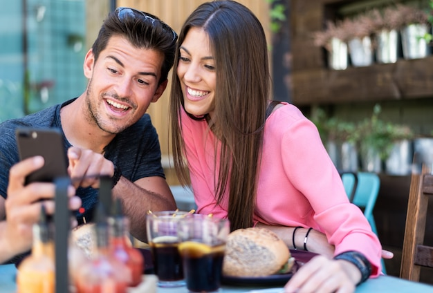 Szczęśliwa młoda para miejsc siedzących na tarasie restauracji ze smartfonem