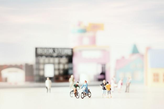 Szczęśliwa młoda para miniaturowa na przejażdżce rowerowej (miniatura) na przejażdżce rowerowej po mieście. walentynki z selektywną ostrością i stonowanym delikatnym pastelowym kolorem.