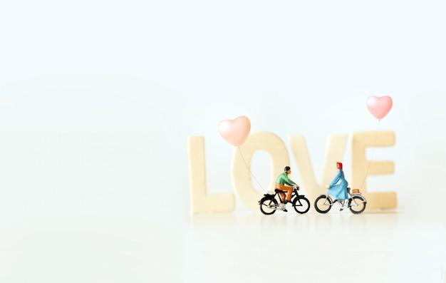 """Szczęśliwa młoda para miniaturowa na rowerze z tekstem """"love"""". walentynki z motywem w stylu vintage."""