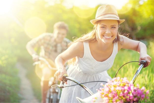 Szczęśliwa młoda para na rowerze przez park