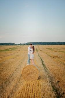 Szczęśliwa młoda para na słomie, koncepcja romantycznych ludzi, piękny krajobraz, sezon letni.