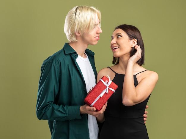 Szczęśliwa młoda para na walentynki mężczyzna daje pakiet prezentów kobiecie, która dotyka włosów, patrząc na siebie na białym tle na oliwkowozielonej ścianie
