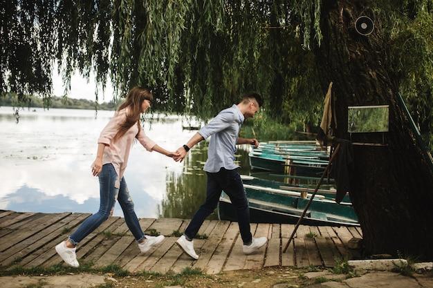 Szczęśliwa młoda para na zewnątrz. młoda miłość para biegnie wzdłuż drewnianego mostu trzymając się za ręce.