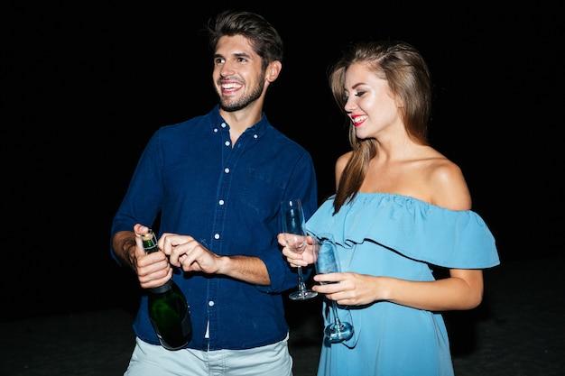 Szczęśliwa młoda para otwiera butelkę szampana na plaży w nocy