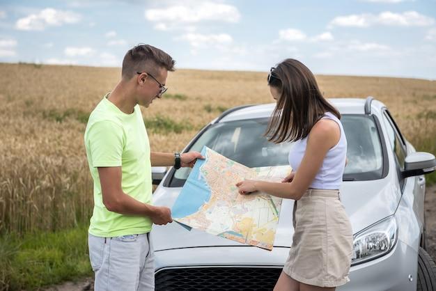 Szczęśliwa młoda para patrząc na mapę drogową w pobliżu samochodu. czas letni