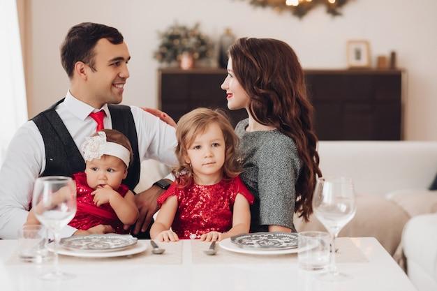 Szczęśliwa młoda para patrząc na siebie siedząc z dziećmi ubrani na czerwono przy stole