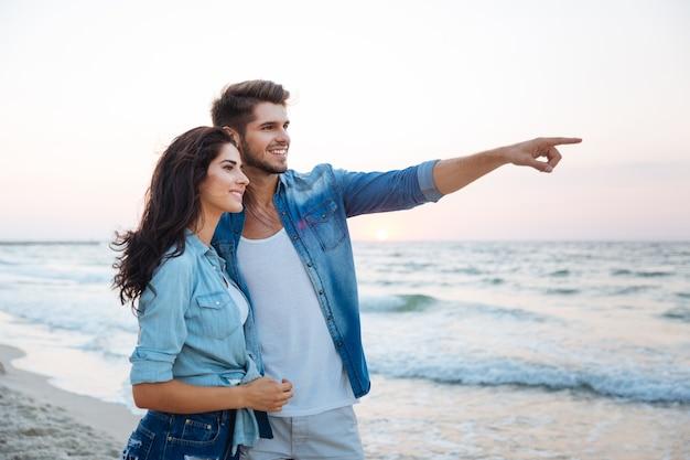 Szczęśliwa młoda para patrząca i wskazująca na plażę