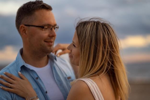 Szczęśliwa młoda para piękny kaukaski na zachód słońca na plaży latem piękne niebo na tle