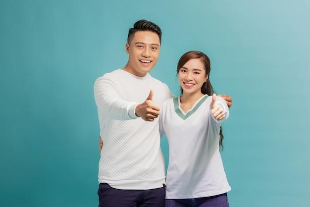 Szczęśliwa młoda para piękny pokazując kciuk do góry i patrząc w kamerę na jasnoniebieskim