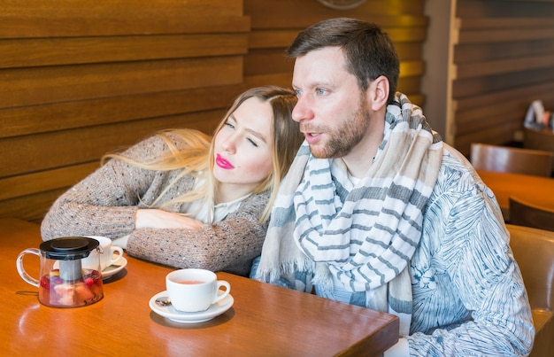 Szczęśliwa młoda para pije kawę i uśmiecha się siedząc w kawiarni.