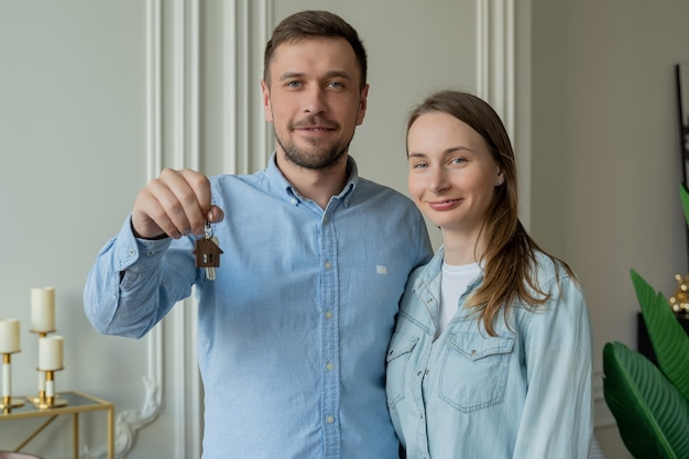Szczęśliwa młoda para pokazuje nowe klucze własnego domu młoda uśmiechnięta para pokazuje klucze do nowego domu przytulanie