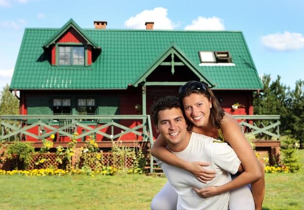 Szczęśliwa młoda para przed ich nowym wiejskim domem