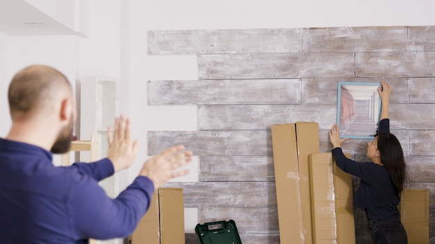 Szczęśliwa młoda para przeprowadza się do nowego mieszkania wiszący obraz na ścianie. praca zespołowa w parze.