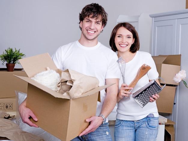 Szczęśliwa młoda para przeprowadza się do nowego mieszkania