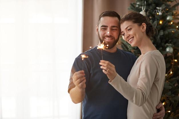 Szczęśliwa młoda para przytula się do choinki i patrzy na płonące ognie