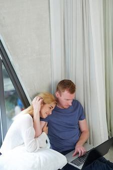 Szczęśliwa młoda para przytula się i ogląda nowy rozrywkowy program na laptopie podczas pobytu w hoje z powodu pandemii koronawirusa