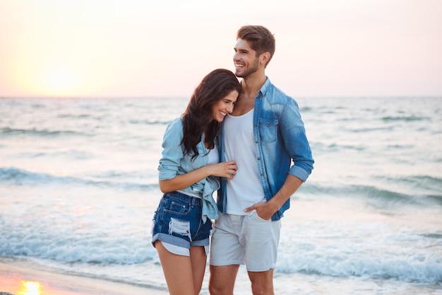 Szczęśliwa młoda para przytulająca się i śmiejąca się na plaży