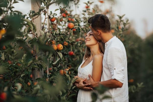 Szczęśliwa Młoda Para Przytulanie Się W Jesiennym Sadzie Wśród Dojrzałych Czerwonych Jabłek. Premium Zdjęcia
