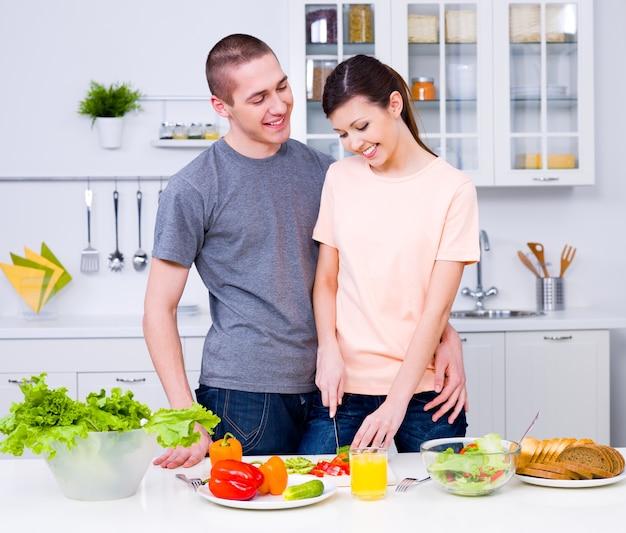 Szczęśliwa młoda para razem przygotowywać śniadanie w kuchni