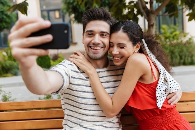 Szczęśliwa młoda para robi sobie zdjęcie selfie na telefonie komórkowym i przytula się siedząc na ławce na zielonej ulicy