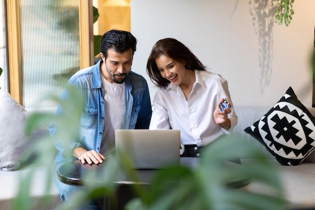 Szczęśliwa młoda para rodzina zakupy online z komputera przenośnego. dokonywanie zakupów online koncepcja.