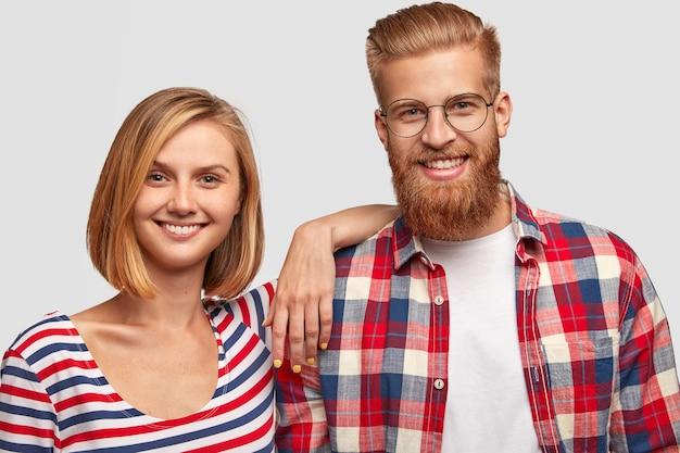 Szczęśliwa młoda para rodziny z wesołymi minami, ubrana niedbale, ma białe zęby, stoi blisko siebie. optymistyczny hipster z rudą brodą i koszulą w kratkę ma randkę z dziewczyną