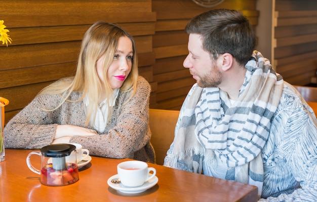 Szczęśliwa młoda para rozmawia i pije kawę i uśmiecha się siedząc w kawiarni.