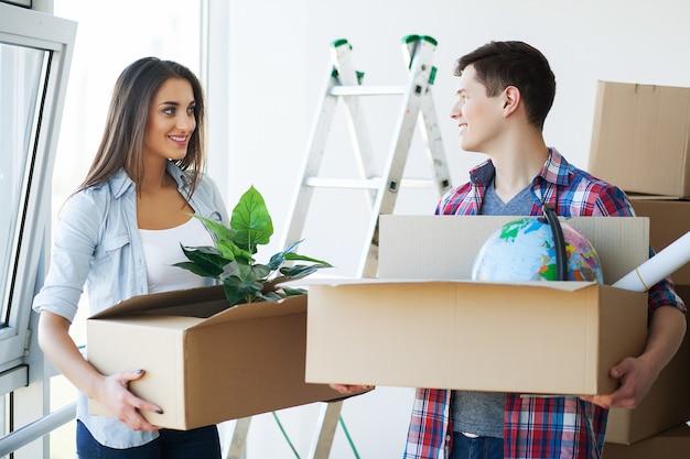 Szczęśliwa młoda para rozpakowywania lub pakowania pudełka i przeprowadzka do nowego domu