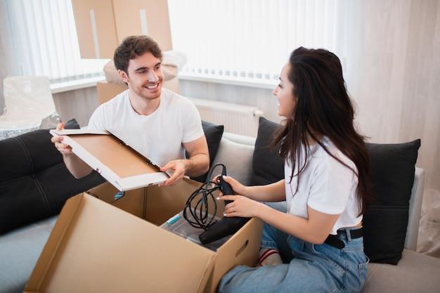 Szczęśliwa młoda para rozpakowywanie lub pakowanie pudeł i przeprowadzka do nowego domu.