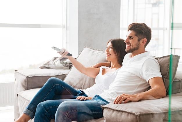Szczęśliwa młoda para siedzi i ogląda telewizję w domu