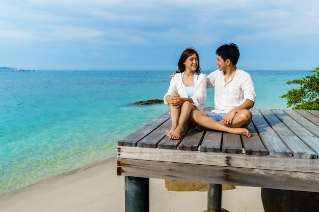 Szczęśliwa młoda para siedzi na drewnianym moście i plaży morskiej na wyspie koh munnork, rayong, tajlandia