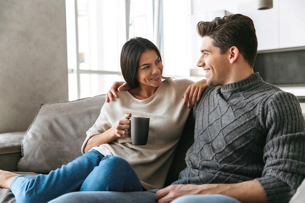 Szczęśliwa młoda para siedzi na kanapie w domu, oglądając telewizję