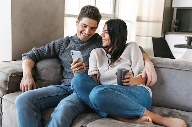 Szczęśliwa młoda para siedzi na kanapie w domu, pijąc herbatę
