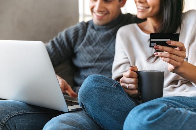 Szczęśliwa młoda para siedzi na kanapie w domu przy użyciu komputera przenośnego