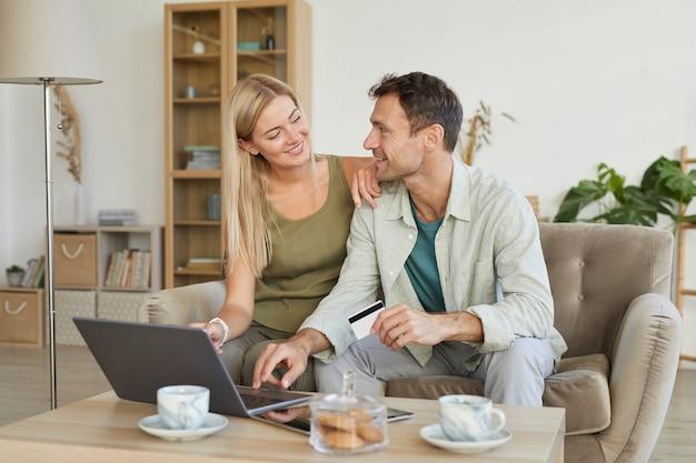 Szczęśliwa młoda para siedzi na kanapie w salonie i rozmawia ze sobą podczas korzystania z laptopa razem