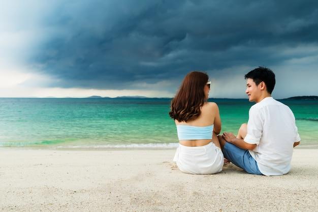 Szczęśliwa młoda para siedzi na plaży na wyspie koh munnork, rayong, tajlandia