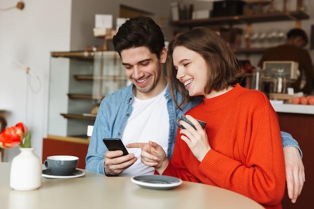 Szczęśliwa młoda para siedzi przy stoliku kawiarnianym