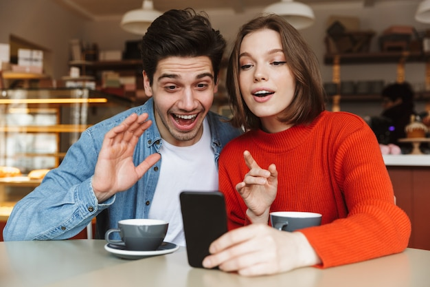 Szczęśliwa młoda para siedzi w kawiarni