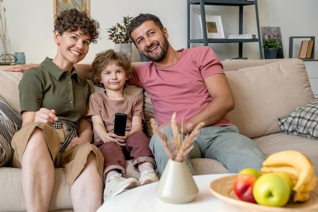 Szczęśliwa młoda para śmieje się z programu telewizyjnego siedząc na kanapie w salonie z ich uroczym synkiem między nimi