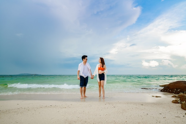 Szczęśliwa młoda para spaceru na plaży na wyspie koh munnork, rayong, tajlandia